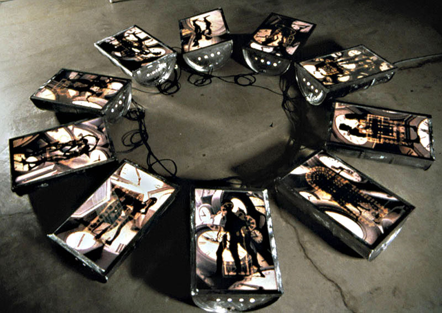 Chronos, 1999, installation view, color transparencies, 10 halved fifty-five gallon barrels (light box), 240 x 240<br><br>Ouranos covered and copulated with Gaia until their son Kronos became angered and castrated him, separating sky from earth and becoming known as the creator of time. The color transparencies overlay male and female figures with ten influential cathedrals and Arman clocks.
