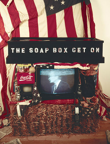 Get on the Soap Box, 1992, installation view, C-Prints, gelatin silver prints, wood light box, video, hay bale, flags, found objects, 48 x 96 x 36
