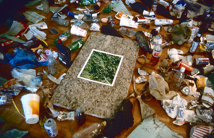 Your Litter Invades Your Space, 1998, installation detail, C-Print, 14 x 11, granite, 33 x 22, collected trash, 144 x 84<br><br>Viewers collect trash outside the gallery and place around a photograph of verdant grass on granite.